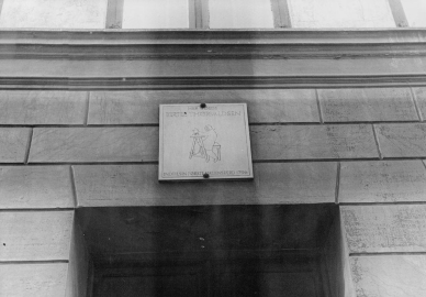 Mindetavlen over indgangsdøren til Åbenrå 13. Mindetavlen blev skænket af stenhuggermester Peter Schannong i 1935. Mindetavlens skæbne ved husets nedrivning kendes ikke.